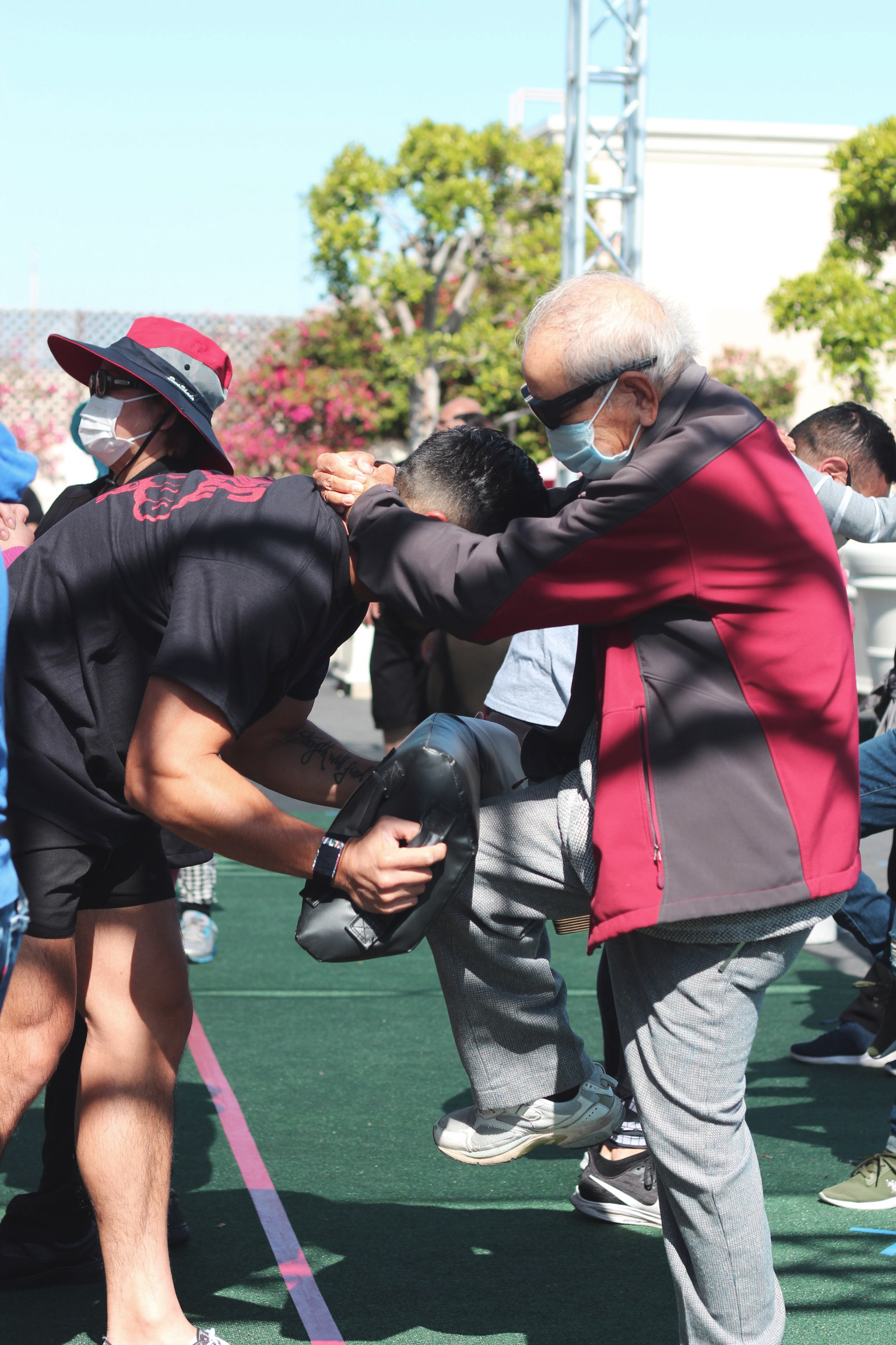 elderly man kneeing thai pads